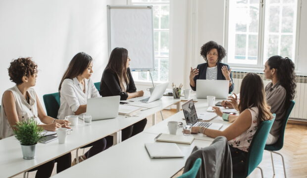 Group of female latin women having a business meeting. Sitting at the table in conference room, working on laptops or making presentations. Taking selfies and posing for business portraits.